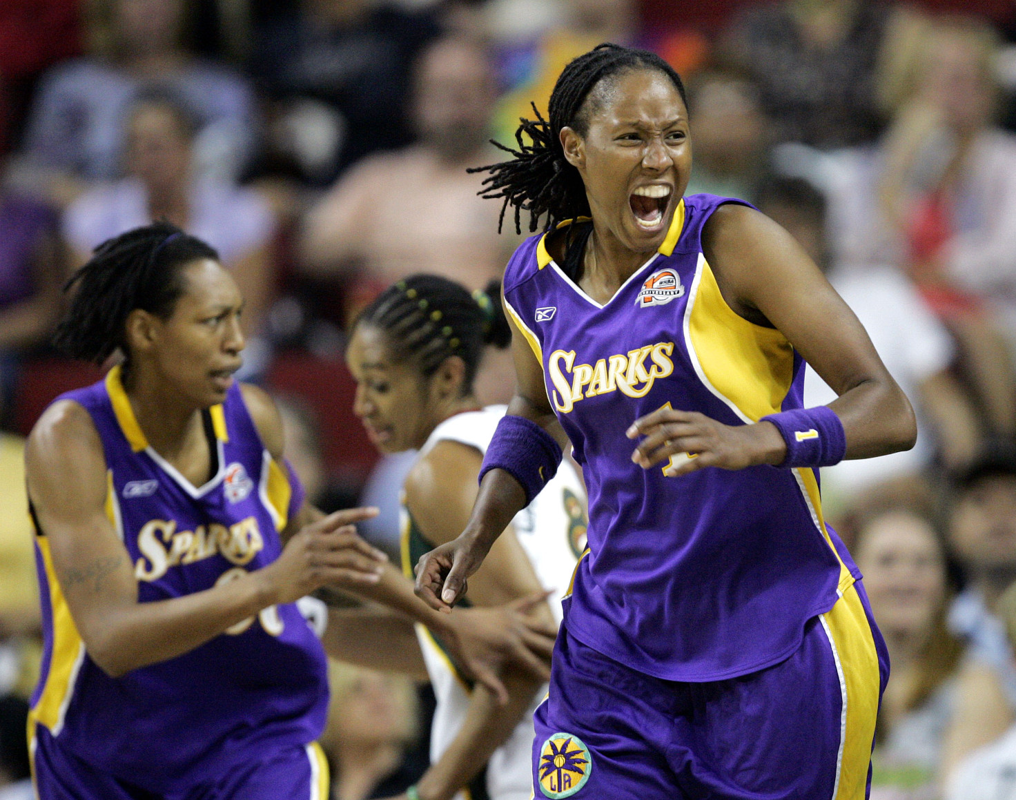 Los Angeles Sparks' Chamique Holdsclaw, right, yells out as she hobbles upcourt after being injured in the first quarter against the Seattle Storm during a WNBA first-round playoff basketball game, Friday, Aug. 18, 2006, in Seattle. She's followed by teammate Murriel Page, left, and Seattle Storm's Iziane Castro Marques. Holdsclaw returned to the game in the quarter. (AP Photo/Elaine Thompson)
